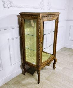 Антикварная витрина с мраморным навершием и желто-зеленой шелковой внутренней отделкой.